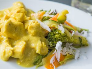 Foto do prato chicken curry com coco fresco e legumes