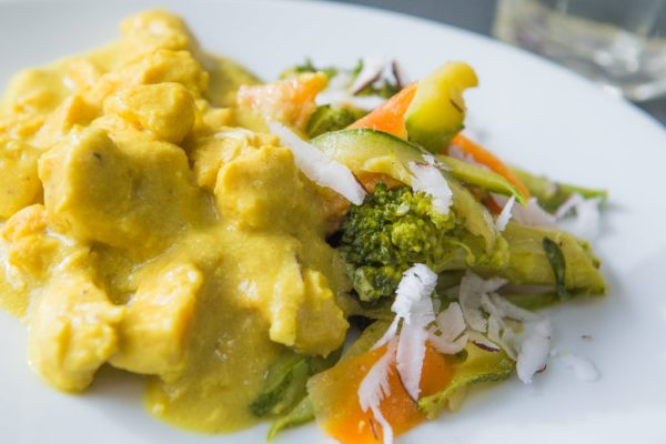 Foto do prato chicken curry com coco fresco e legumes